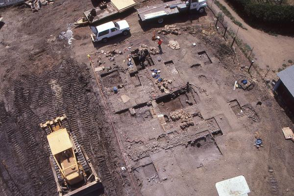 Aerial shot of excavation showing stone adobe foundations and dark soil Chinese refuse pits.