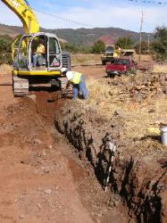 Sandy Thomas monitors trenching for water main through prehistoric sites.